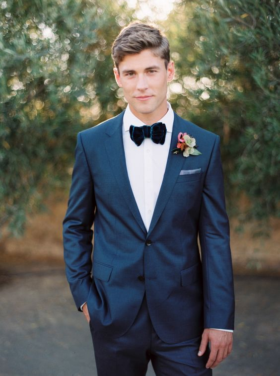 a navy suit, a white shirt, a navy velvet bow tie and a simple boutonniere for a gorgeous look