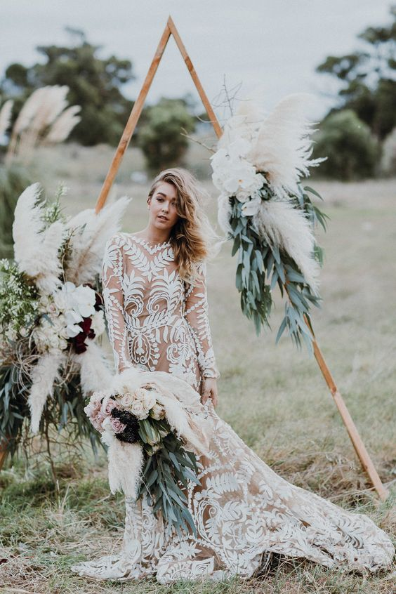 a nude boho wedding dress with white lace, a mermaid silhouette, long sleeves and a train