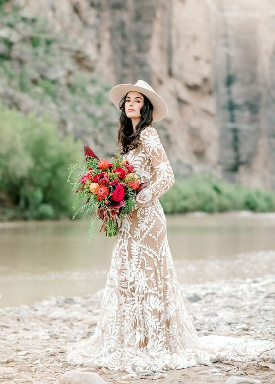 a nude lace boho A-line wedding gown with long sleeves, a high neckline and a train