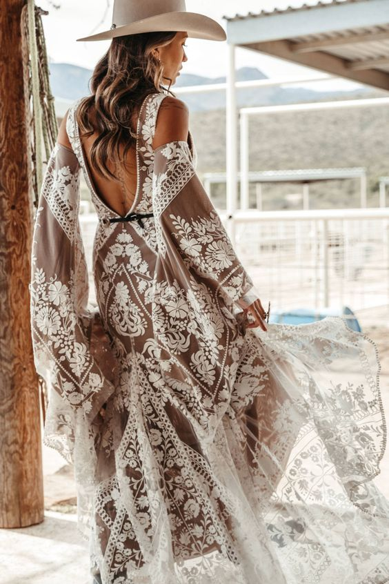 a nude lace boho wedding gown with open shoulders, an open back, bell sleeves and an A-line skirt with a train