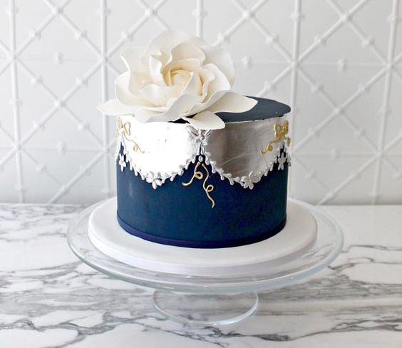 a one tier wedding cake in navy and silver foil, with patterns and an oversized white sugar bloom on top