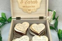 a plywood box filled with plywood hearts that are to be signed by the guests and accented with a burlap ribbon