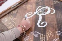 a reclaimed wood sign with a monogram can be signed by the guests and then hung on the wall as an artwork