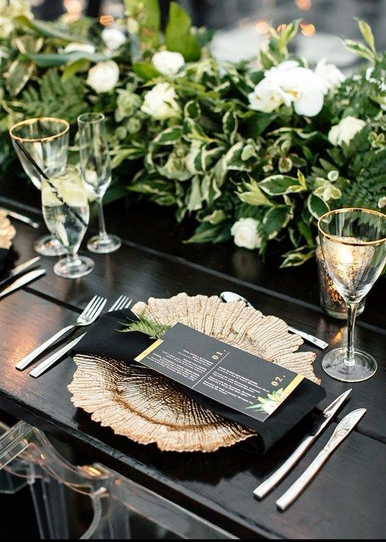 a refined wedding tablescape with a black table, a chic gold charger and greenery and white blooms