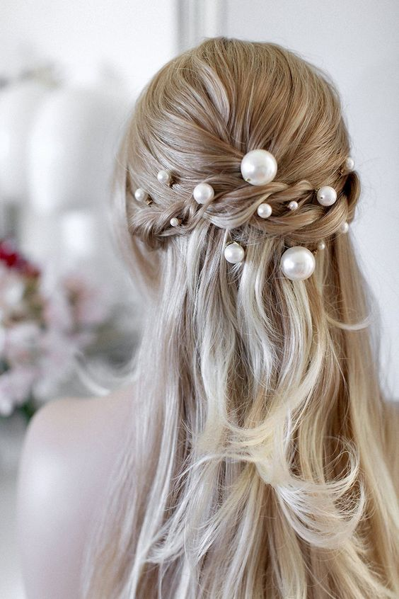 a romantic half updo with a braid halo accented with pearl pins of various sizes looks really chic and cool