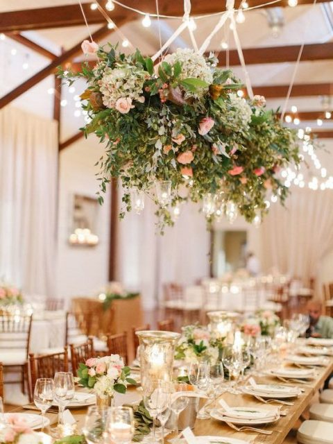 a romantic overhead decoration of greenery, hydrangeas, pink roses and candle holders