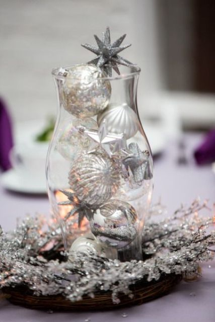 a shining winter wedding centerpiece of a wreath with silver snowflakes and a vase with silver ornaments