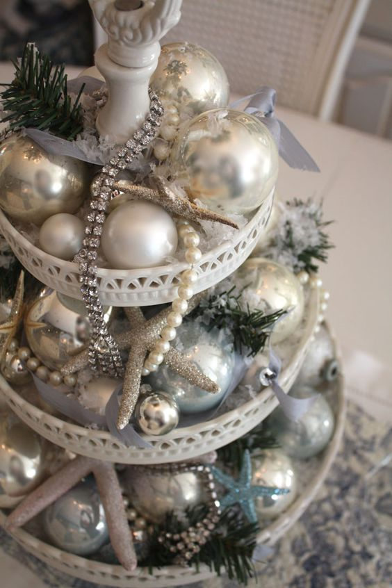 a sparkling beach Christmas wedding centerpiece of a stand with silver and blue ornaments, glitter starfish and beads and sparkles