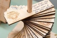 a stand with thin plywood pieces and names and a date burnt on them is a creative and cool wedding guest book
