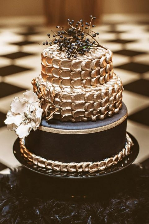 a stylish black and gold wedding cake with shiny tiers and a sugar bloom plus privet berries on top