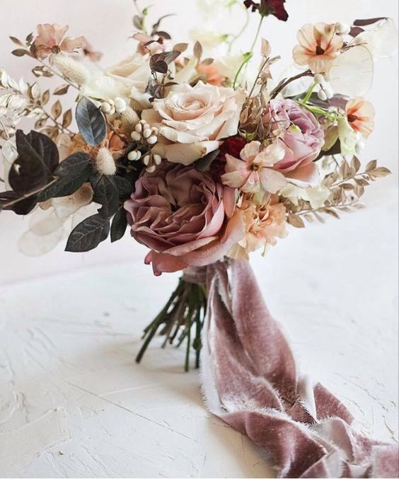 a tender summer wedding bouquet with mauve, ivory and blush blooms and some foliage plus mauve ribbons