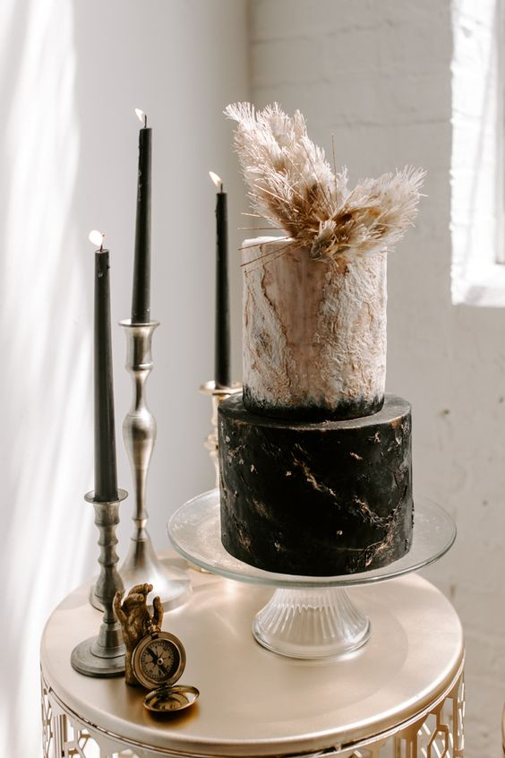 a textural white and black wedding cake with gold leaf and pampas grass and fronds is a very refined option