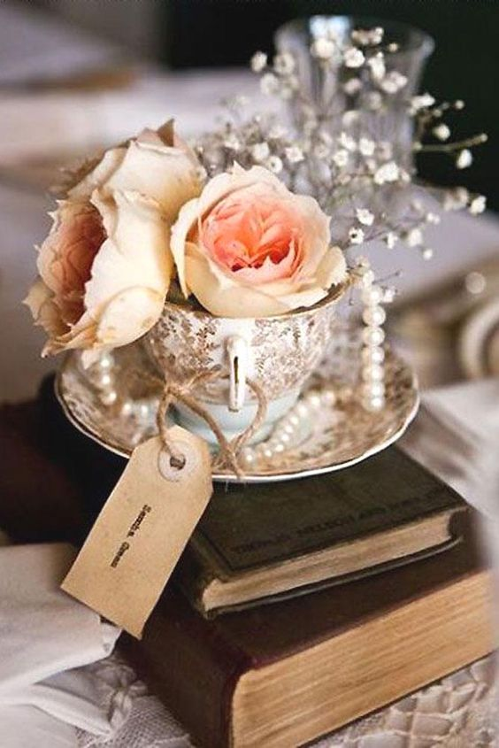 a vintage wedding centerpiece of a book stack, a tag, a vintage cup with blooms and soem pearl strands