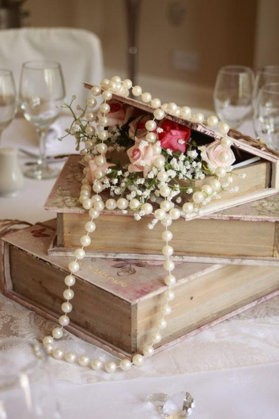 a vintage wedding centerpiece of a stack of books, blooms and stands of pearls looks super elegant and very chic