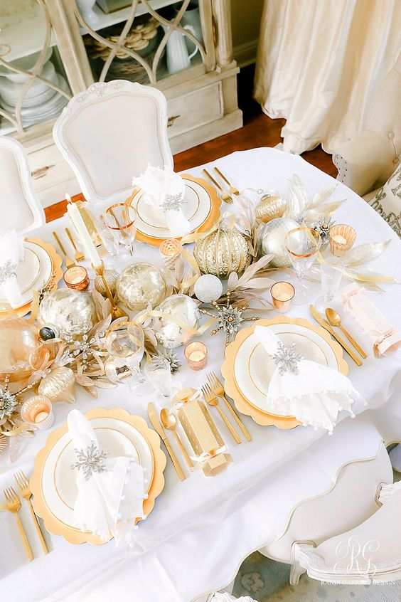a wedding table runner done in silver and gold, with oversized ornaments and fake foliage plus candles