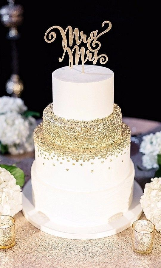 a white and gold polka dot wedding cake with a gold calligraphy topper is a lovely glam wedding piece to enjoy