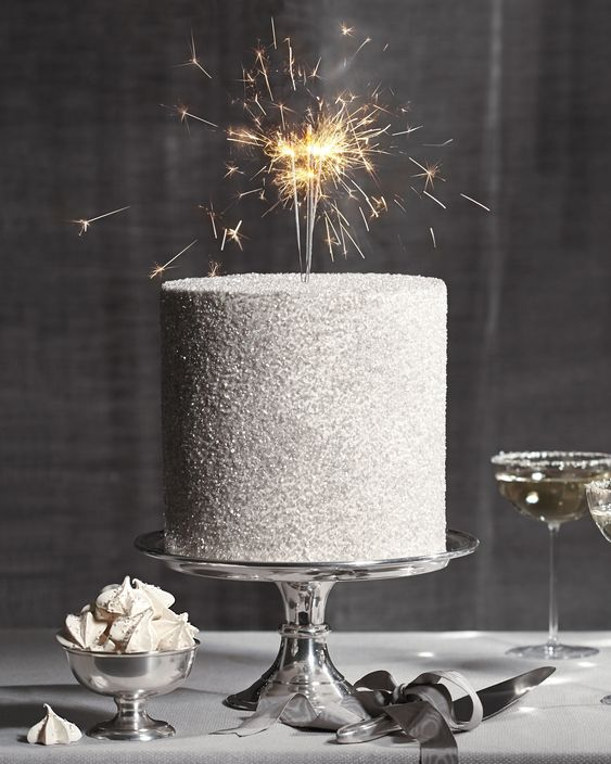 a white glitter wedding cake with sparklers is a stylish glam idea to go for, it's simple and very bright
