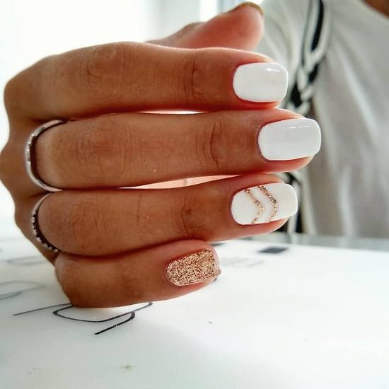 a white manicure with a gold glitter chevron and a gold glitter accent nail is a very elegant and fresh option