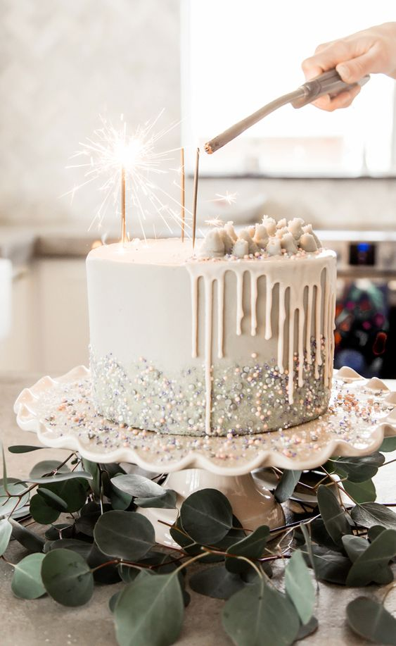 a white wedding cake with beads, glitter and pieces of white chocolate on top plus sparklers is very modern and lovely