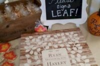 a wood pallet with painted leaves and a sign – your guests will sign each leaf separately