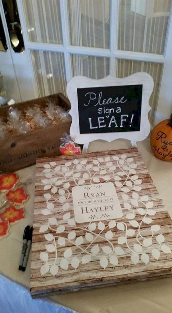 a wood pallet with painted leaves and a sign - your guests will sign each leaf separately