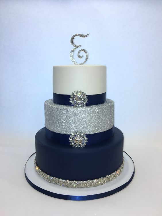 an elegant white, silver and navy wedding cake with glitter, embellishments and an embellished monogram on top