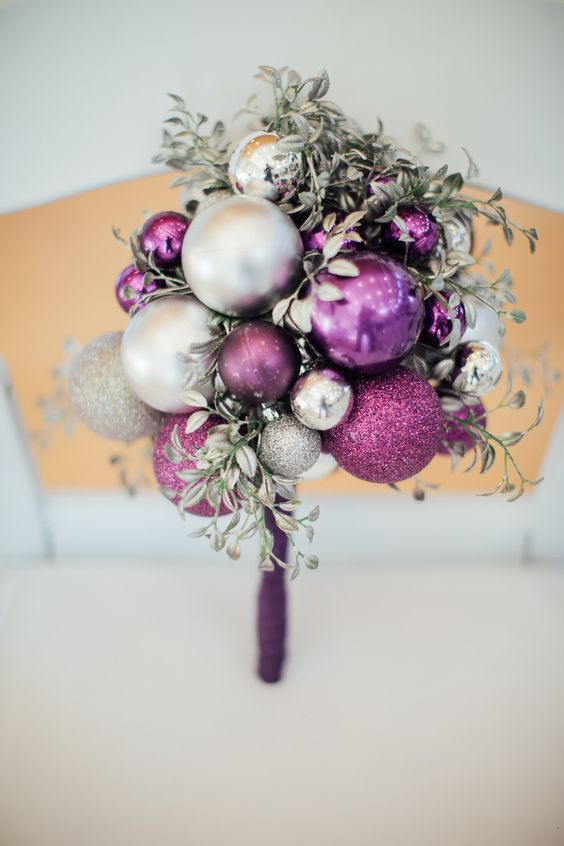 an unusual wedding bouquet composed fully of Christmas ornaments of various shades and silver foliage