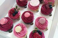 chocolate and vanilla cupcakes with berry icing, fresh berries, cookies and various macarons on top
