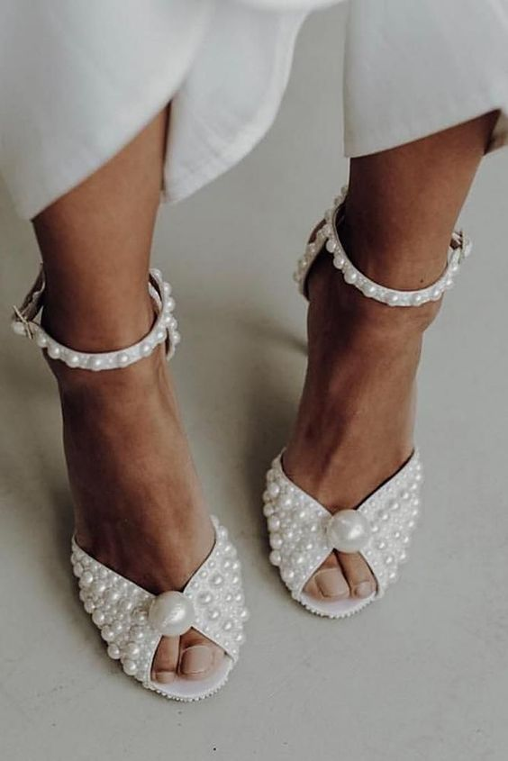 glam and refined wedding shoes fully covered with pearls and with large pearls on top look wow