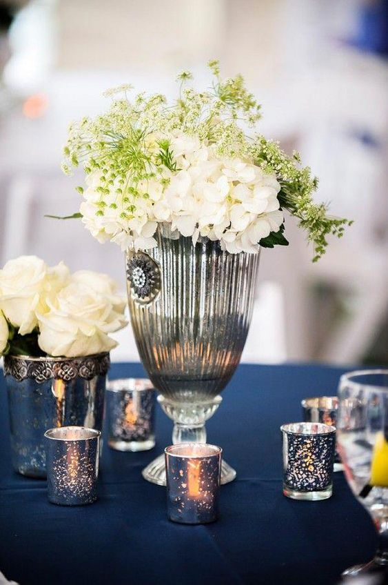 gorgeous wedding table decor - a navy tablecloth, silver mercury glass candles and a vase with white blooms