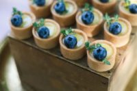 mini tarts with custard and bluberries on top are a very cool and refreshing idea for a wedding