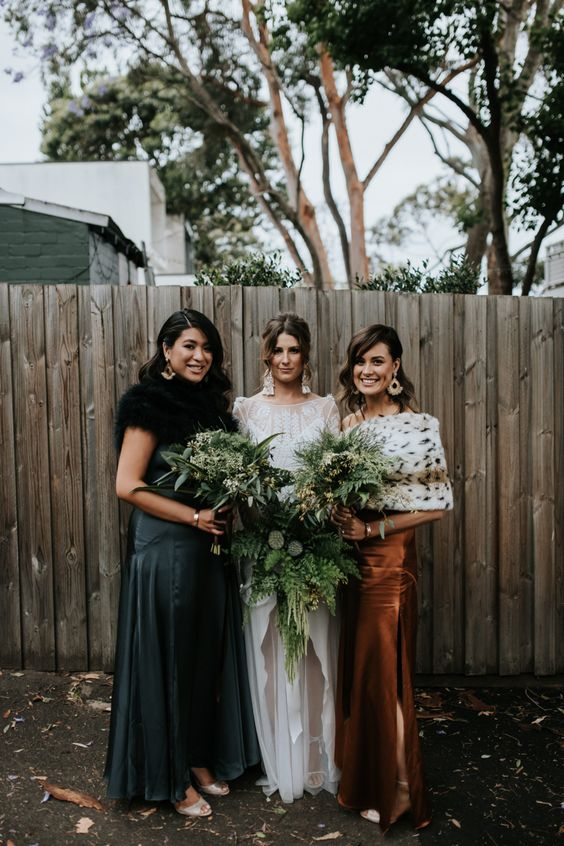 mismatching jewel tone bridesmaid dresses and mismatching coverups for an ultimately stylish bridesmaid look