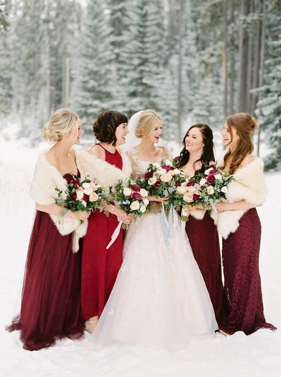 neutral faux fur coverups make the red bridesmaid dresses stand out and accent them a lot
