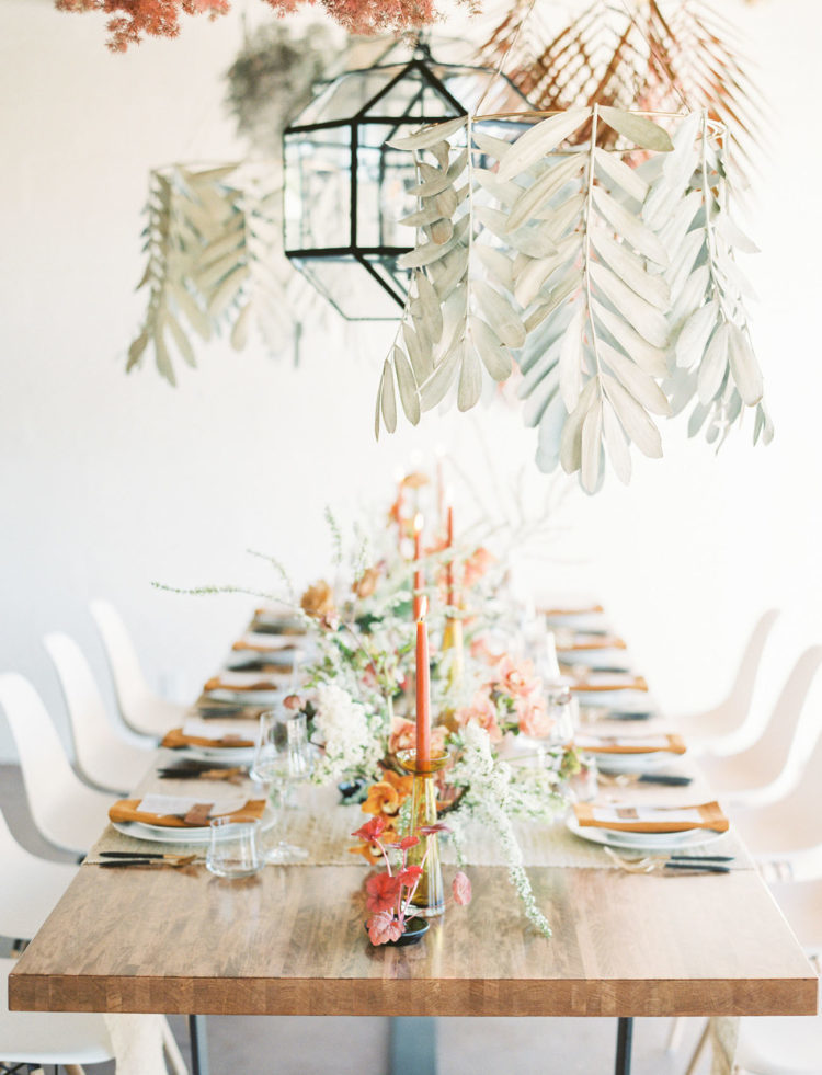 pale and dried leaves and candleholders hanging from above make the reception look bolder and cooler
