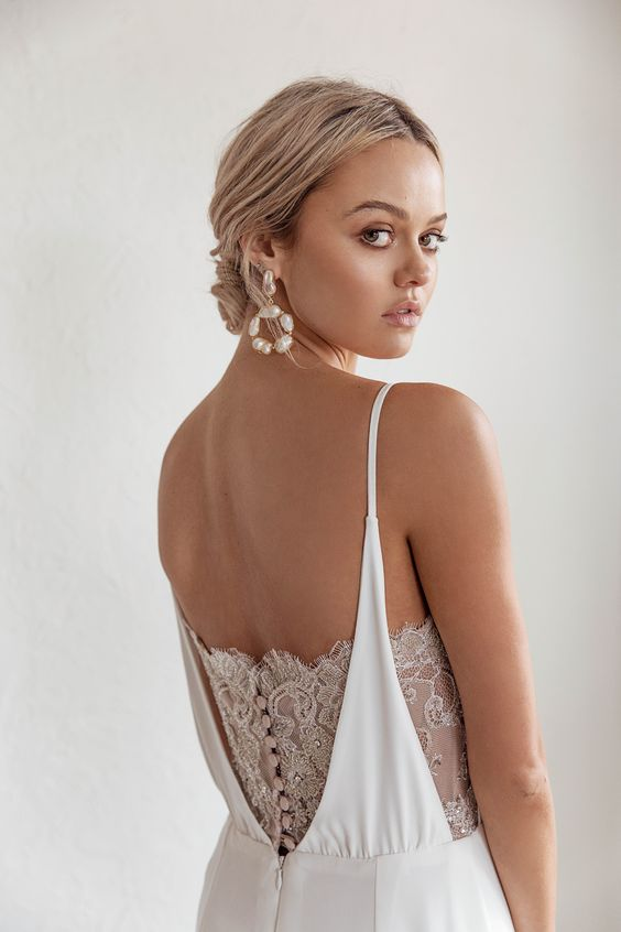 statement baroque pearl earrings and matching pearl buttons accenting the back of the wedding dress