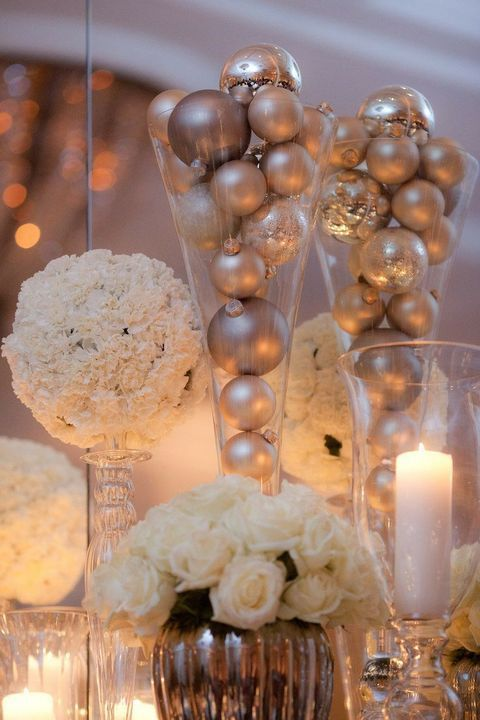tall glass vases with metallic ornaments, pillar candles and lush white bloom arrangements for decor