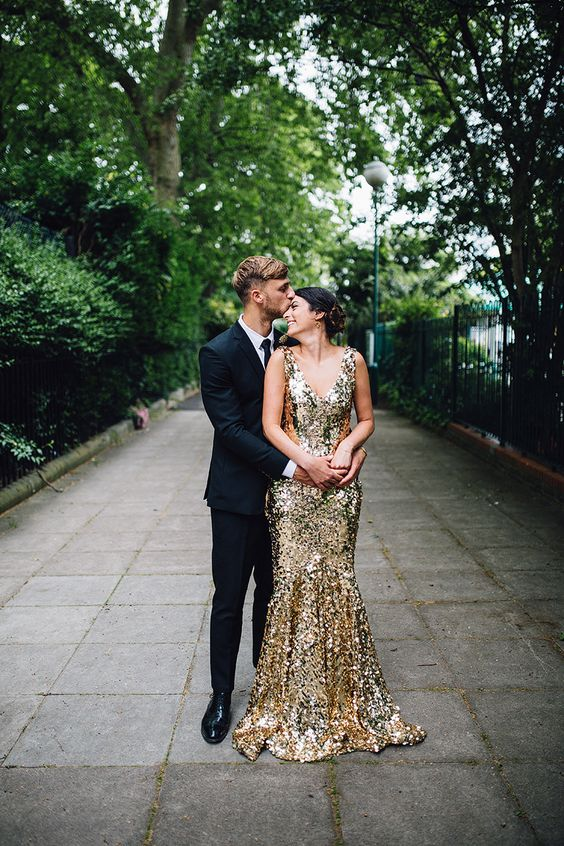 the groom wearing a black suit and a tie and the bride rocking a gold wedding dress with a train
