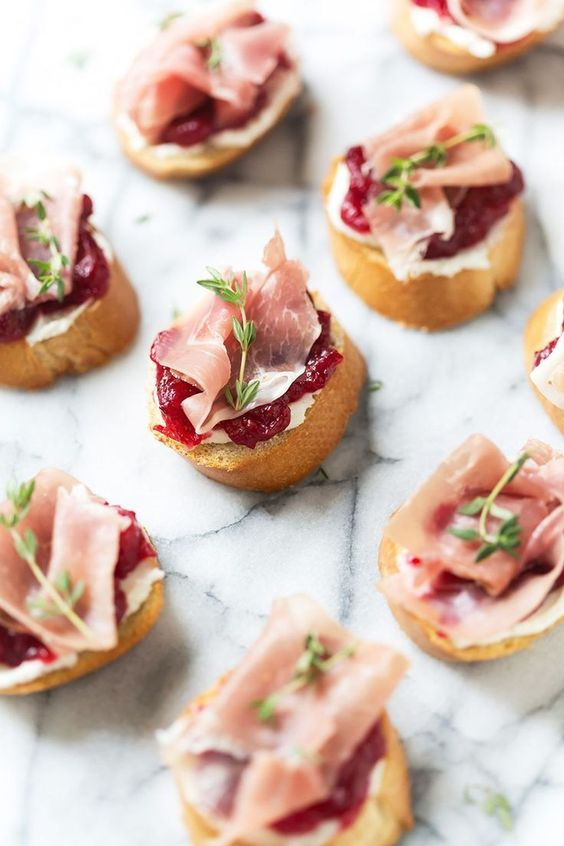 toasts with cranberry jam, cream cheese, proschiutto, herbs for a winter or Christmas wedding
