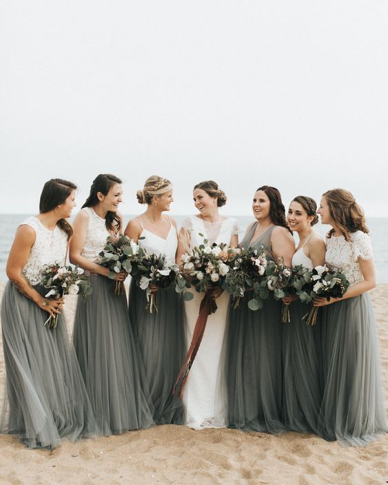 white lace crop tops and dark green maxi skirts for the bridesmaids and a dark green maxi gown for the maid of honor