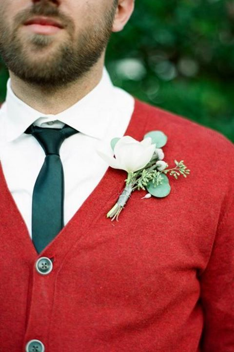 a Christmas groom look with a white shirt, a green tie, a red cardigan and a white floral boutonniere is very bold