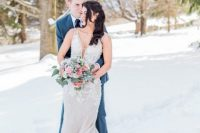 a beautiful sheath wedding dress with a train, lace appliques and a covered plunging neckline