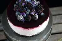 a blackberry and blueberry wedding cheesecake with an oreo base topped with fersh blooms, blackberries and blueberries