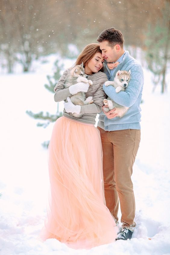 a blue shirt, a grey sweater, a peachy pink bow tie, tan pants and black shoes for a winter groom
