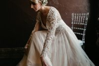 a blush and ivory lace wedding dress with a deep V-neckline and long sleeves and a messy updo with blooms