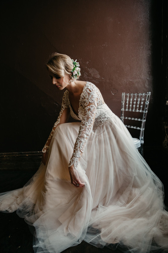 a blush and ivory lace wedding dress with a deep V neckline and long sleeves and a messy updo with blooms