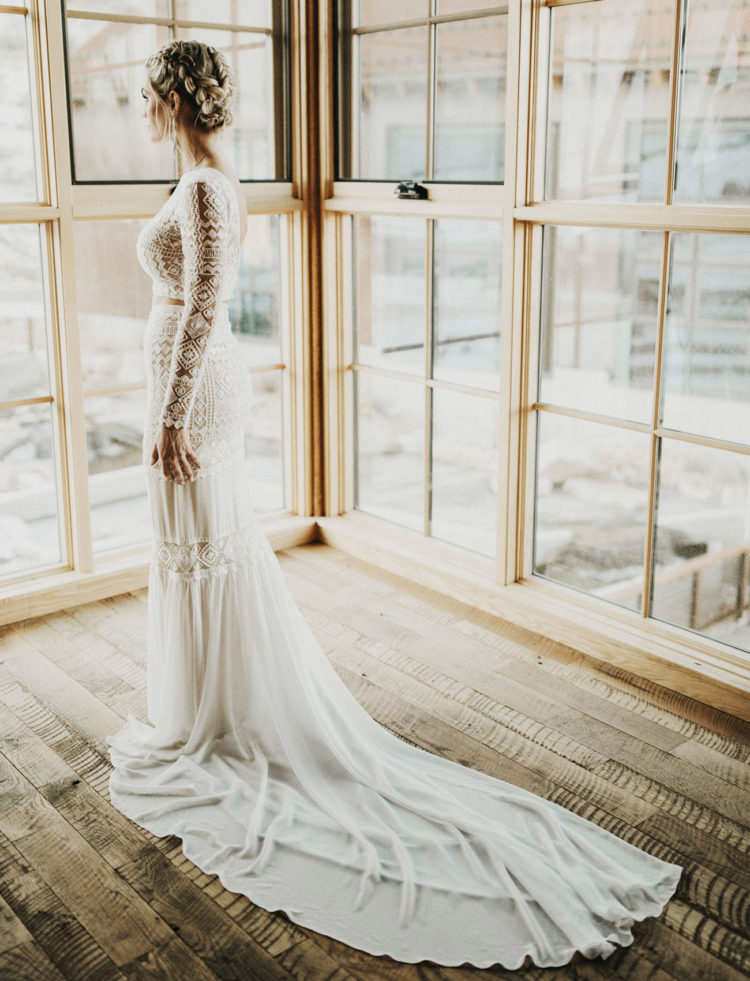 a boho lace two piece wedding dress with a train, a braided updo and statement earrings