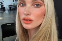 a bold makeup with brown eyeshadow, accented eyebrows, a bold orange lip, blush and cool fresh skintone is chic