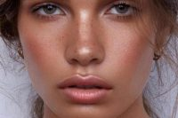 a bronze makeup with a shiny pink lip, shiny skin and bronzer, trendy eyebrows and coral blush is wow