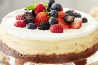 a cheesecake on a chocolate base topped with fresh berries is a crowd-pleasing wedding dessert idea