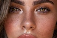 a chic and shiny natural makeup with a shiny touch, a glossy nude lip, a bit of highlighter and brown eyeshadows plus accents on the eyes